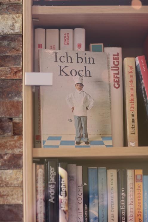 Kochbücher zieren in großen Regalen das Café