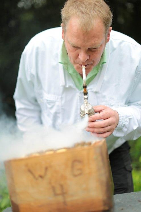 Mike Gerdes stößt mit der Imkerpfeife etwas Rauch in den Kasten