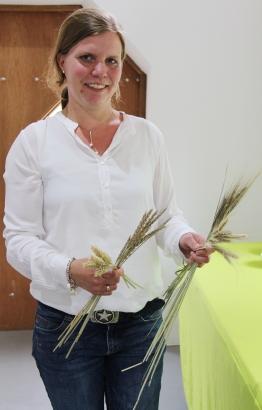 Petra Schulze Westerhoff zeigt Ähren vom Weizen, Dinkel, Emmer und Norddeutschem Champagnerroggen (v.l.).