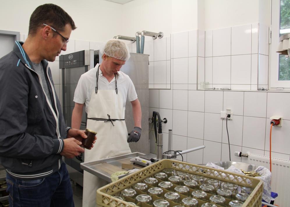 Dietmar Heinker (l.) ist bei der Abfüllung behilflich.