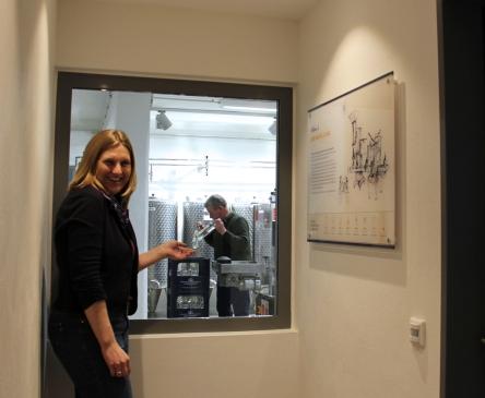 Anne Gerbermann im Bereich der Abfüllung, die Gäste durchs Fenster verfolgen können.